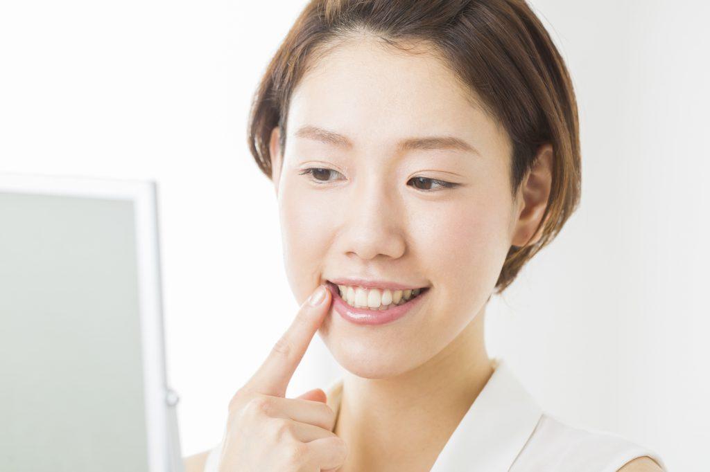 鏡で歯を見る女性